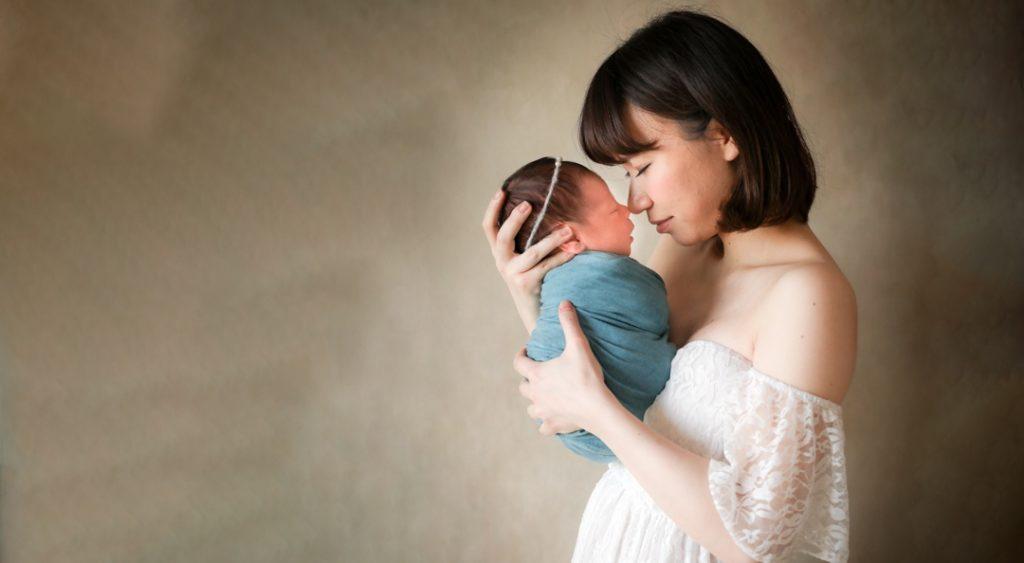お母さんが新生児の赤ちゃんを抱っこしている写真