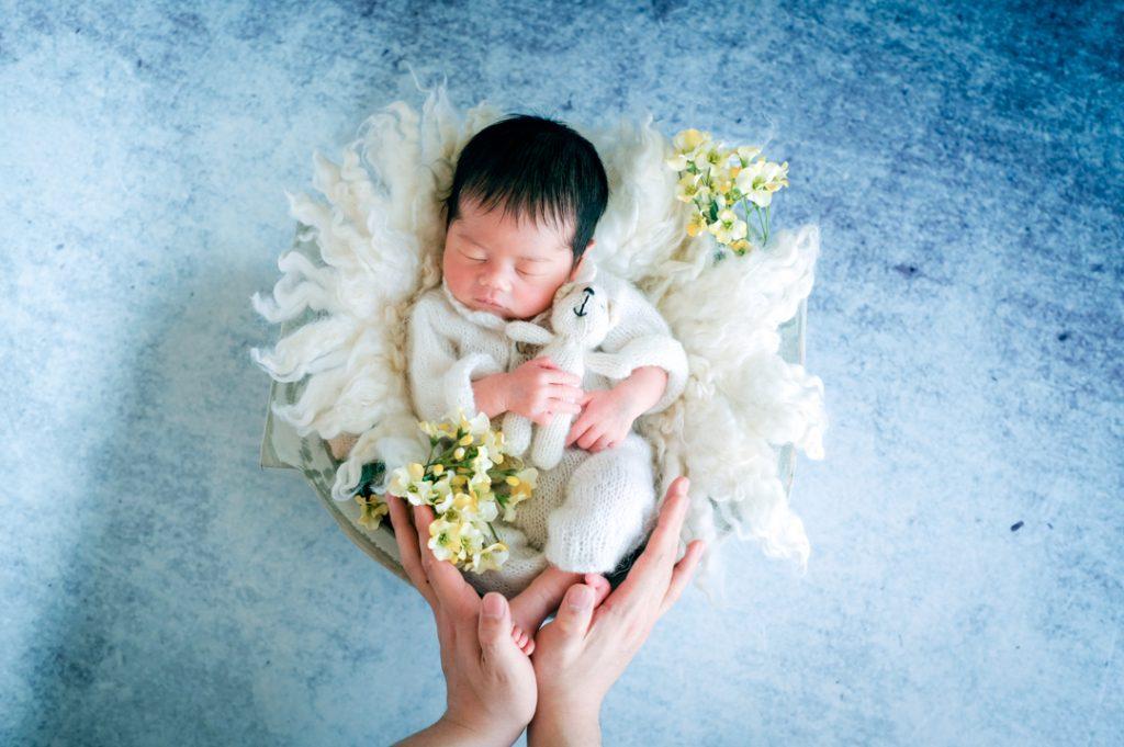 白い服を着ているカゴで寝ている赤ちゃんのニューボーンフォト